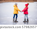 Adorable little girls skating on the ice-rink 57982657