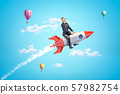 Young businessman riding toy rocket in blue sky with hot air balloons in background. 57982754
