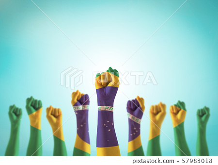 Brazil flag on people hands with clenched fists raising up for labor day, republic proclamation day, national holiday celebration and stay strong for Brazilian power isolated on blue sky background 57983018