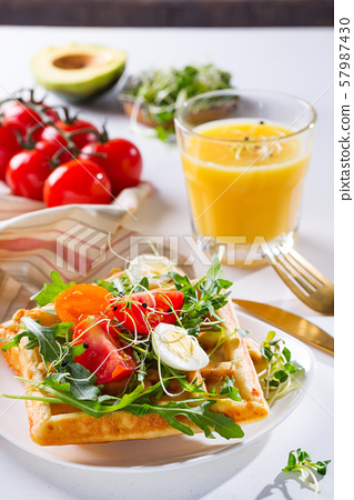 Fresh baked sweet belgian waffles with eggs, tomatoes, micro green and avocado served on a plate 57987430