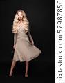 Gorgeous blonde model in ivory dress on black. 57987856