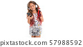 Girl in sparkling dress choosing song in black smartphone and holding red plastic bottle with sipper 57988592