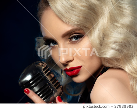 Portrait of pretty blond female singer holding microphone 57988982