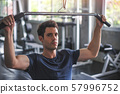 Handsome weightlifter lifting barbells working out 57996752
