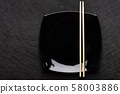 Empty black plate with chopsticks on dark background. Japanese food style. Top view with copy space 58003886