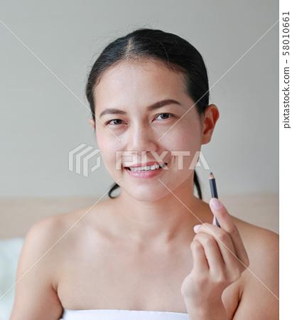 Beautiful young woman using a pencil makeup. 58010661