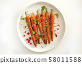 Baked organic carrots with honey, parsley, cheese and flax, pumpkin, sunflower seed on plarte. Top 58011588
