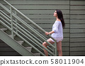 Beautiful young woman climbing industrial stairs 58011904