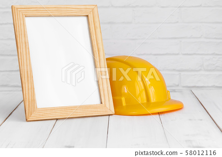 Photo frame and safety hat on white wood table 58012116