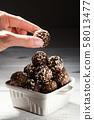 Woman hand taking raw vegan energy ball. homemade 58013477