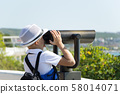 Rear view of little boy in white hat watching through telescope at sunny day in vacation from 58014071