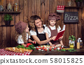 Mother and daughters reading recipe book 58015825