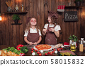 Cheerful girls having fun with sausage in kitchen 58015832