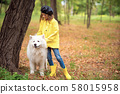 Lovely girl on a walk with a beautiful dog in a park outdoor 58015958