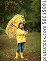 Happy funny child girl with umbrella in rubber boots 58015991