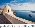 The Aegean sea and the Catholic Church of St. Stylianos in the city of Fira in Santorini Island 58017698