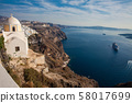 The Aegean sea and the Catholic Church of St. Stylianos in the city of Fira in Santorini Island 58017699