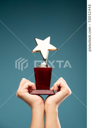 IImage of hands of man raising goblet with star 58032448