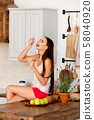 Cute girl sitting on kitchen table and eating 58040920