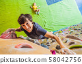 Muscular man practicing rock-climbing on a rock wall indoors 58042756