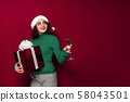 Beautiful smiling woman in santa claus hat, warm green Christmas sweater holding a glass of 58043501