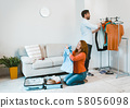 Family travel, husband and wife packing luggage for vacation. 58056098