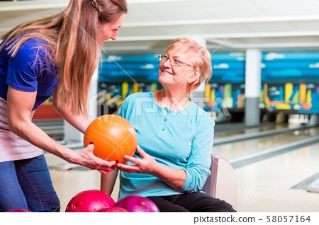 Mother giving bowling ball to her daughter 58057164