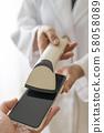 เภสัชกรหญิงในชุดคลุมสีขาวสแกนบาร์โค้ดสำหรับลูกค้าที่ชำระเงินด้วยเงินสดในเวลาที่ชำระเงิน 58058089