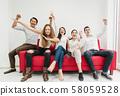 Friends in casual wear celebrating winning or 58059528