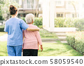 nurse caregiver support walking with elderly woman 58059540