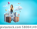Scared giant young woman covering mouth with hands, standing amid high-rise buildings that are 58064149