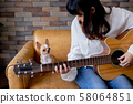 Attractive female playing guitar with pet 58064851