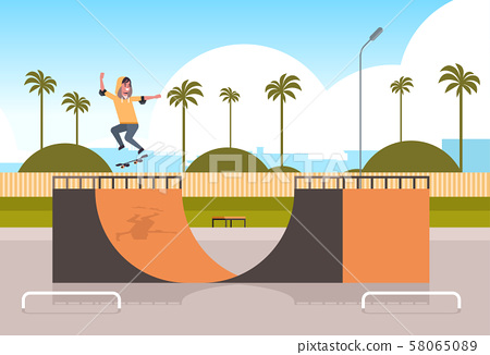 male skater performing tricks in public skate board park with ramp for skateboarding teenager having 58065089