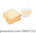 Bread with pouring condensed milk in cup on white background. 58067152