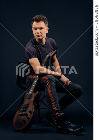 Low key portrait of musician sitting on chair with 58068856