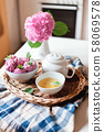 Pink cupcakes, mug of green mint tea, white teapot and hydrangea flowers on kitchen table. 58069578