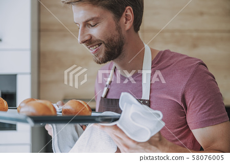 Man being satisfied with a result of his cooking 58076005
