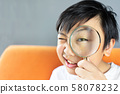 Little boy holding Magnifying glass 58078232