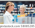 Chemist and customer standing in pharmacy between the shelves 58085285