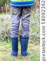 Boy standing on the green wearing blue wellies 58092362