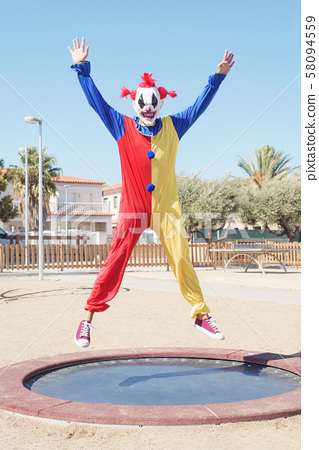 scary clown jumping outdoors 58094559