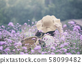 Woman wearing sun hat and bamboo basket visiting Verbena flower field. Image with film camera filter. 58099482