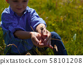 Boy catched the butterfly in the hands 58101208