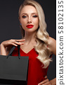 Beautiful girl with blond hair, classic make-up in a elegant red dress and shopping bag. Beauty face 58102135