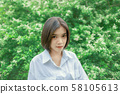 Portrait of an Asian woman in a garden full of leaves 58105613