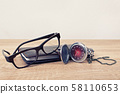 Pocket watch, glasses and a planner on a table 58110653