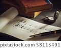 Music notes and old book with pocket watch on wooden table background in morning light. Writing chords by vintage pen. Closeup and copy space for text. Concept of Music lovers. 58113491