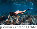 Woman freediver with fins underwater. Freediving in blue ocean 58117669