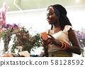 Pleased brunette woman looking at unordinary flowers 58128592