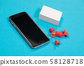 Black mobile phone, a pile of white scratch paper and red push pins are lying on pale-blue surface 58128718